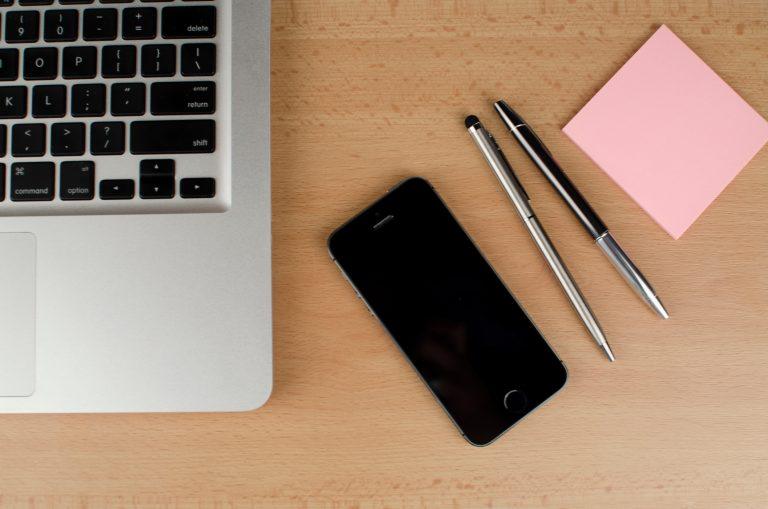 Computador, celular, lápices y post-it en una mesa que reflejan el trabajo remoto o a distancia.